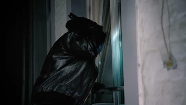vídeos de stock e filmes b-roll de masked burglars breaking is a house - ladrão