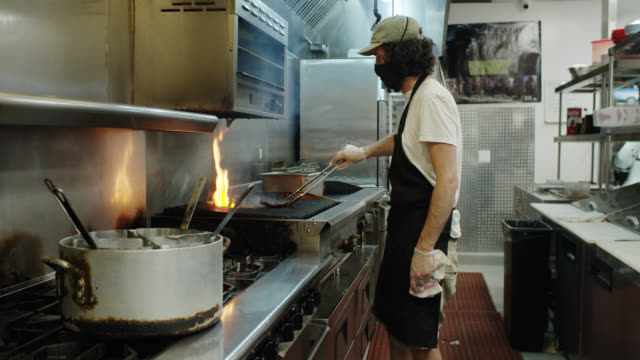 vídeos de stock e filmes b-roll de masked chef grilling food for takeout during covid-19 outbreak - covid restaurant