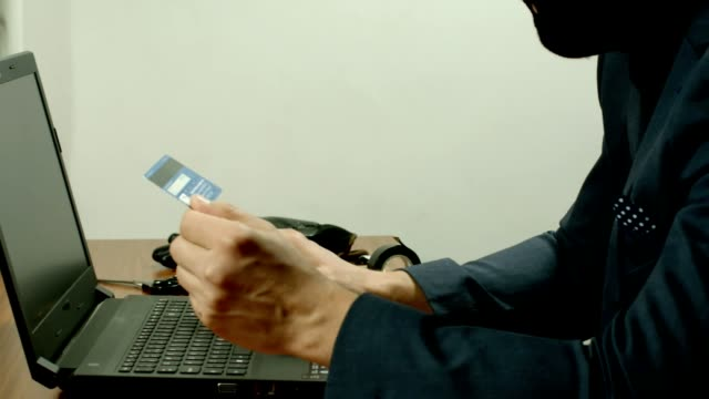 A Masked Criminal Wearing A Suit Holding A Fake Credit Card To Perform Fraud Online. video