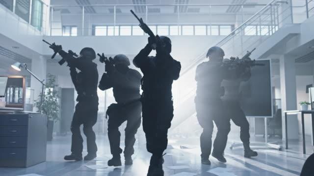 maskiertes feuerwehrteam der bewaffneten swat polizeibeamten stürmt ein ebendes büro mit desken und computern. soldaten mit rifles bewegen sich nach vorne und decken umliegende ab. - dominanz stock-videos und b-roll-filmmaterial