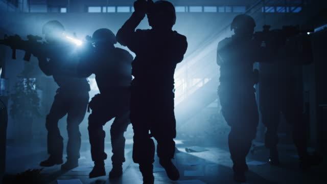 maskiertes feuerwehrteam der bewaffneten swat polizisten storm ein dark seized office building mit desks und computern. soldaten mit gewehre und taschenlampen bewegen sich nach vorne und decken die umgebung ab. - dominanz stock-videos und b-roll-filmmaterial