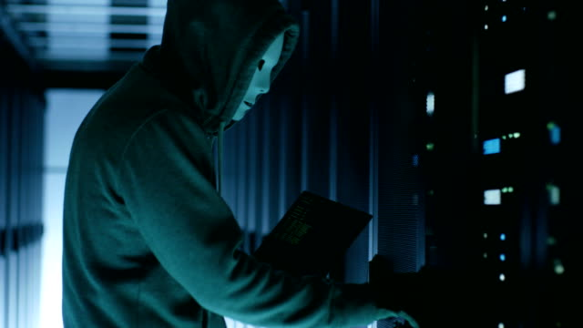 Masked Hacker wearing Hoodie Opens Server Cabinet and Connects to Server with His Notebook. video