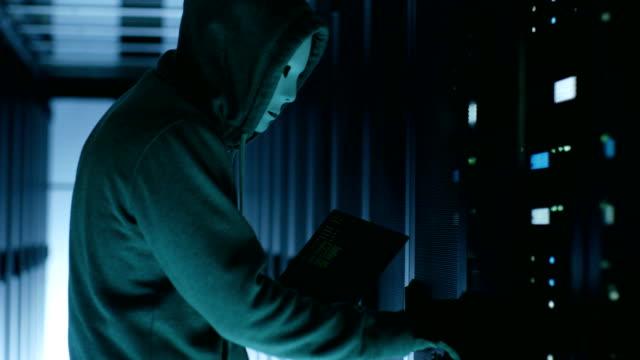 Hacker mascarado vestindo capuz abre gabinete de servidor e conecta ao servidor com seu Notebook. - vídeo