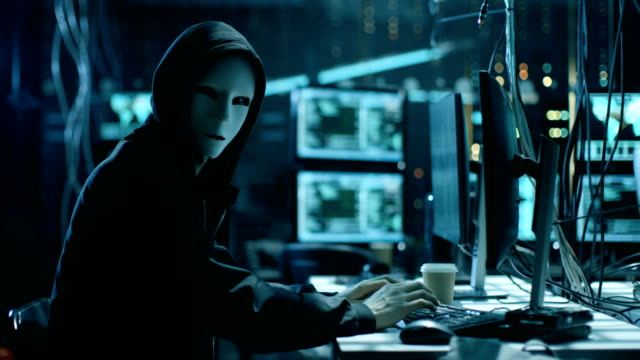 Masked Hacktivist Organizes Massive Data Breach Attack on Corporate Servers. They're in Underground Secret Location Surrounded by Displays and Cables.