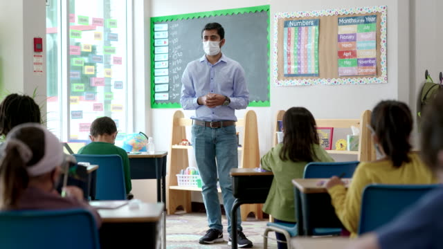 Masked male teacher speaking to students in class Male teacher wearing a protective face mask teaching a group of multi-ethnic group of students in classroom during COVID-19. teacher stock videos & royalty-free footage