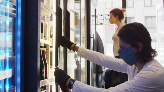 Homme masqué regardant dans le réfrigérateur dans le petit dépanneur avec la femme se distanciant socialement de lui pendant la pandémie de Covid-19 - Vidéo