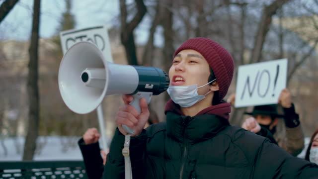 stockvideo's en b-roll-footage met gemaskerde man strike protest coronavirus. crowd people activisten corona virus mers. - aziatische etniciteit