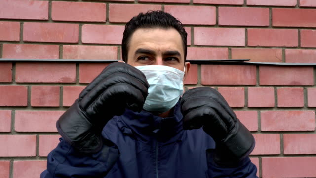 masked man wearing boxing gloves, getting crazy, trying to protect himself from invisible threat, fighting with virus, hypochondriac, paranoia - box name video stock e b–roll