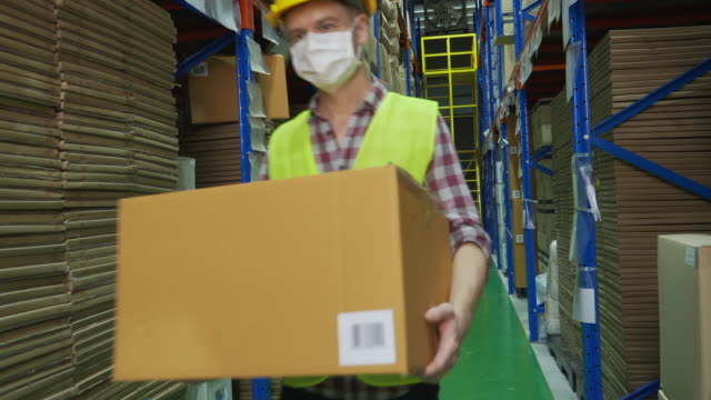 masked man worker who works in warehouse walks holding box, greeting his colleagues with a nod to avoid being touched, working on a new normal concept