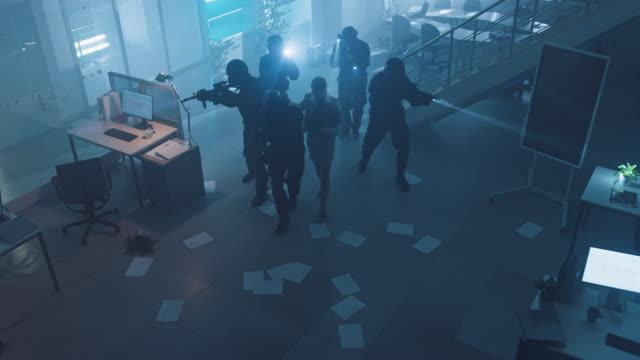 vídeos de stock, filmes e b-roll de esquadrão mascarado de policiais armados swat resgatar uma refém fêmea em um prédio de escritórios escuro apreendido com secretárias e computadores. soldados com rifles e lanternas mover para a frente e cobrir arredores. - domínio