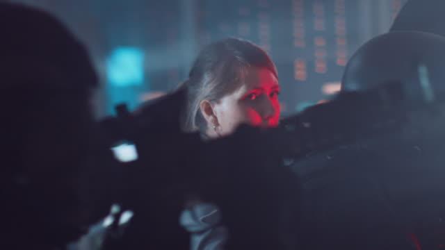 maskierte truppe von bewaffneten swat polizisten rettet eine weibliche geisel in einem dark seized office building mit desks und computern. soldaten mit gewehre und taschenlampen bewegen sich nach vorne und decken die umgebung ab. - dominanz stock-videos und b-roll-filmmaterial