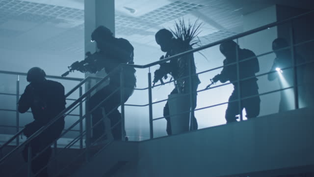 Masked Squad of Armed SWAT Police Officers Run Down the Stairs from a Second Floor in a Dark Office Building. Soldiers with Rifles and Flashlights Move Forwards and Cover Surroundings.