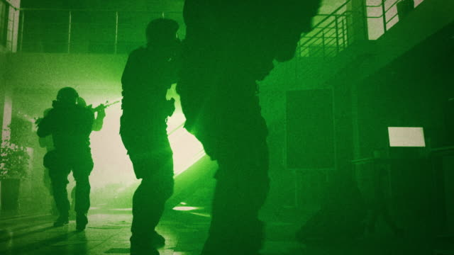 Masked Squad of Armed SWAT Police Officers Slowly Move in a Hall of a Dark Seized Office Building with Desks and Computers. Soldiers with Rifles Cover Surroundings. Green Night Vision Effect.