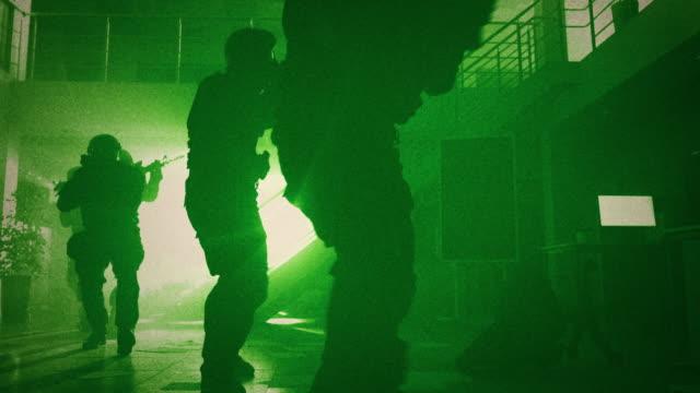 Maskierte Truppe von bewaffneten SWAT Polizeibeamten langsam in einer Halle eines dunklen Seized Office Building mit Desks und Computern. Soldaten mit Rifles decken Umgebung ab Green Night Vision Effect. – Video