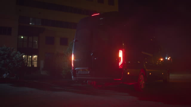 masked team of armed swat police officers exit a black van parked outside of an office building. soldiers with rifles and flashlights run on a street filled with smoke. - furgone video stock e b–roll