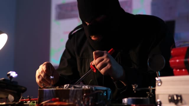 Masked terrorist constructing a time bomb One man, masked terrorist making a time bomb in dark workshop alone. explosive stock videos & royalty-free footage