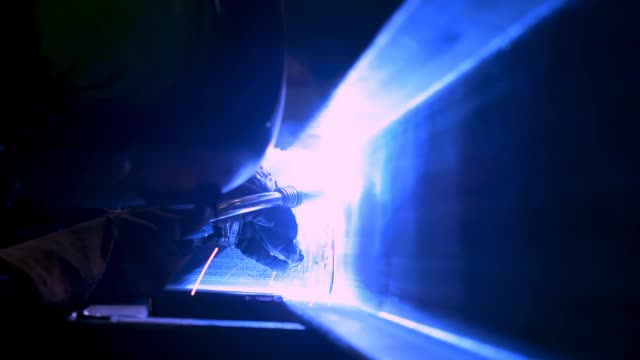 a masked welder is working on welding metal beams. industrial video. close view. - rettificatrice video stock e b–roll