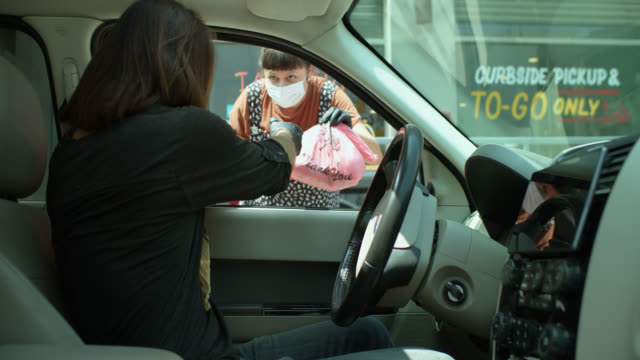 Masked Woman Brings Curbside Order to Man in Car Wearing Bandana Over Face During Covid-19 Lockdown