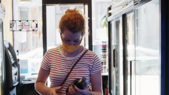 Masked Woman Choosing Wine in Small Convenience Store During Covid-19 Pandemic and Taking it to Counter video
