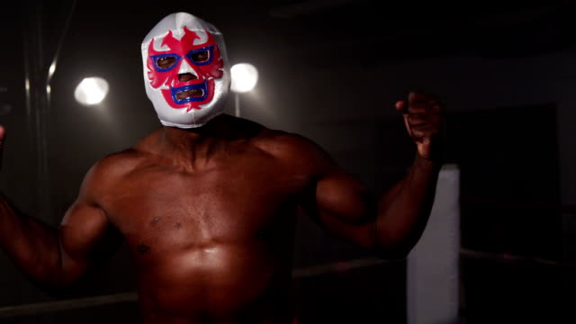 マスクの力士の屈曲の筋肉で威圧的相手 ビデオ