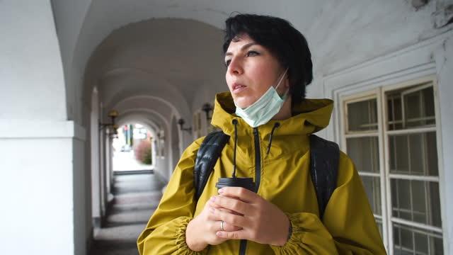 vidéos et rushes de jeune femme masquée avec le café dans les mains attendant une réunion, temps froid. - boisson chaude