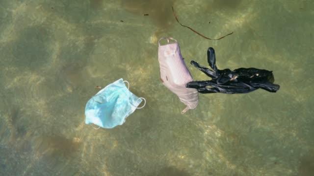 vídeos y material grabado en eventos de stock de máscaras y guantes desechables que contaminan el océano - guante quirúrgico