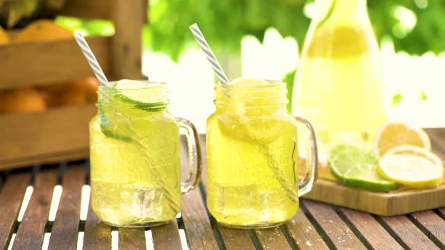 vídeos de stock e filmes b-roll de mason jar glasses of homemade lemonade with slices of lemon and lime - limonada tradicional