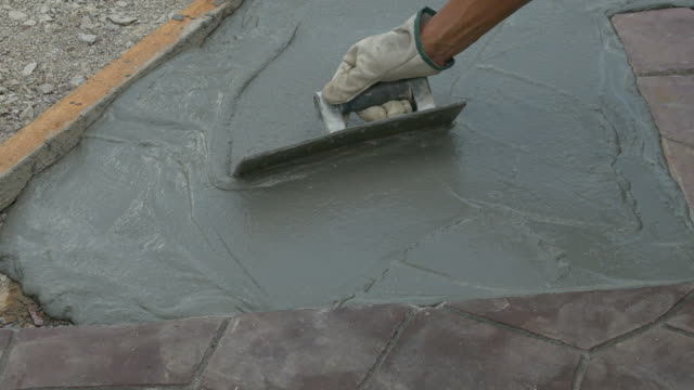 Mason leveling and screeding concrete floor base with square trowel video
