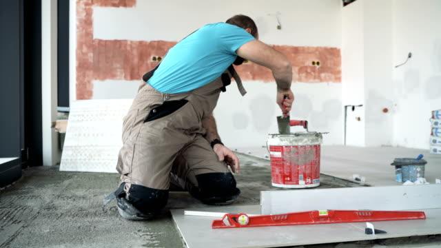 Mason leveling the floor tiles