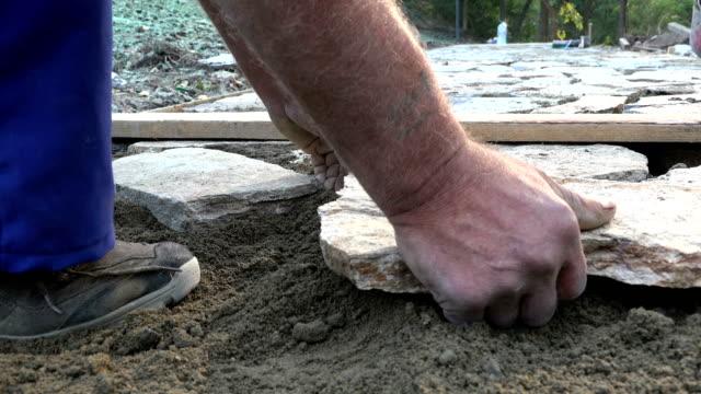 vídeos de stock e filmes b-roll de mason workers making sidewalk pavement with stone blocks - bricolage