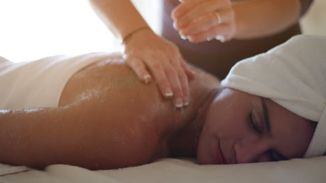 Massage - Body Scrub Treatment A woman in her 30s recieving a massage/body scrub treatment. Filmed in 4k 59.97fps and rendered to 29.97fps ProRes massage oil stock videos & royalty-free footage