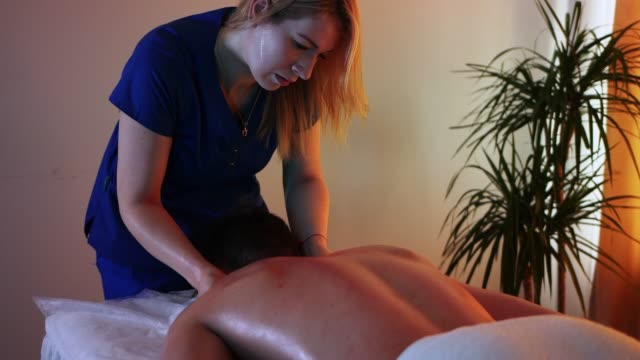 massage session in the spa centre in warm lighting - woman doctor massaging her client's neck - half of his body covered with towel - physical therapy стоковые видео и кадры b-roll