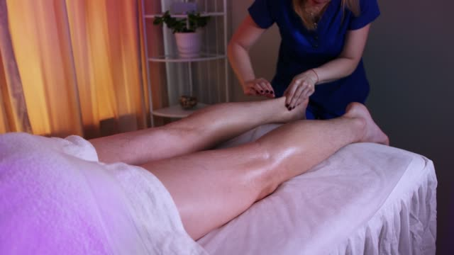 massage session in the spa centre in warm lighting - woman doctor massaging her client's foot - half of his body covered with towel - physical therapy стоковые видео и кадры b-roll