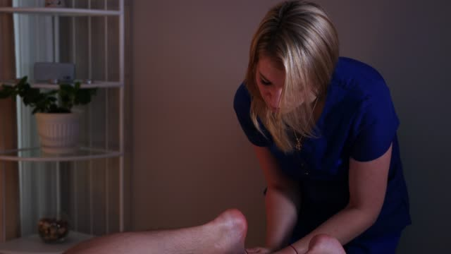 massage session in the spa centre in warm lighting - woman doctor massaging her client's foot - physical therapy стоковые видео и кадры b-roll