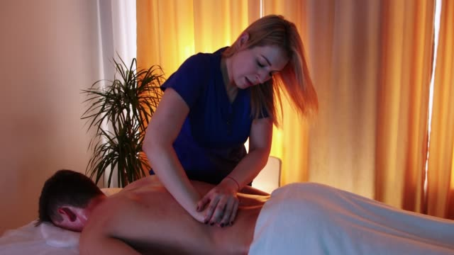 massage session in the spa centre - woman doctor massaging her client's back - physical therapy стоковые видео и кадры b-roll
