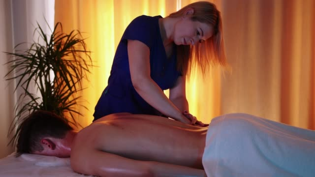 massage session in the spa centre - woman doctor massaging her client's loin - physical therapy стоковые видео и кадры b-roll