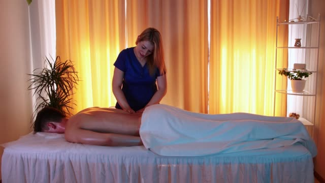 massage session in the spa centre - woman doctor massaging her client's back with oil - physical therapy стоковые видео и кадры b-roll