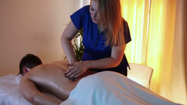 massage session in the spa centre - woman doctor massaging her client's back - half of his body covered with towel - physical therapy стоковые видео и кадры b-roll