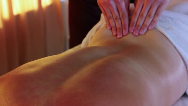 massage session in the spa studio - therapist actively massaging his woman client back - physical therapy стоковые видео и кадры b-roll