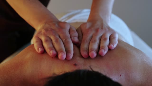 massage session in the spa studio - therapist actively massaging his woman client back using oil - physical therapy стоковые видео и кадры b-roll