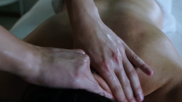 massage session in the spa studio - therapist actively massaging his woman client neck using oil - physical therapy стоковые видео и кадры b-roll