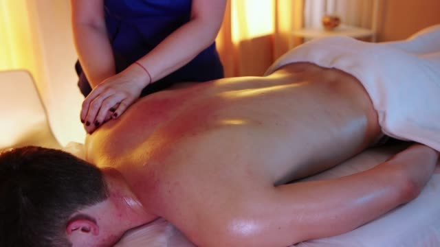 massage session in warm lighting - woman doctor massaging her client's neck using oil - physical therapy стоковые видео и кадры b-roll
