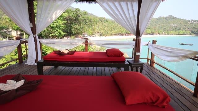 vídeos de stock e filmes b-roll de massage table overlooking the sea. spa massage room on the beach in thailand - mesa mobília