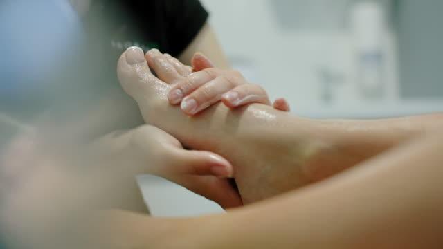 massage therapist doing leg massage to girl. - pedicure filmów i materiałów b-roll