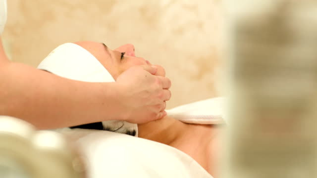 Massage therapy of womans face at beauty spa video