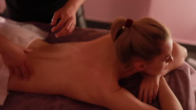 güzellik salonunda masaj tedavi prosedürü. sağlık, cilt bakımı - i̇nsan sırtı stok videoları ve detay görüntü çekimi