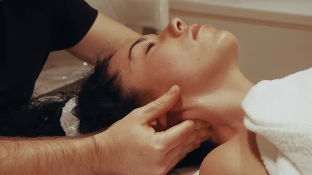 massaging female neck - chiropractor stock videos & royalty-free footage
