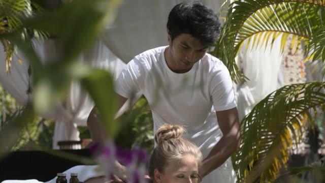 Masseur de trabajo ajuste joven hermosa mujer en el exclusivo complejo turístico - vídeo