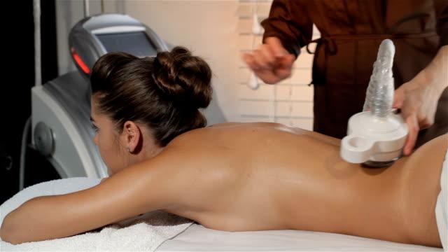 masseur chooses the program on massage machine - затягивание стоковые видео и кадры b-roll