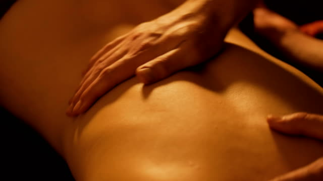 vídeos de stock e filmes b-roll de masseur doing back massage for female client in spa center - massajar